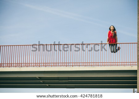 Young long haired girl leaning against railing on the urban bridge. Lifestyle funky in summer. Trendy sport teen jumping in air. - stock photo