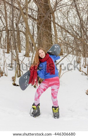 Young long-haired pretty woman in tights snowboarding in winter forest