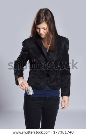 Young long-haired woman pulls from his pocket a roll of dollars - stock photo
