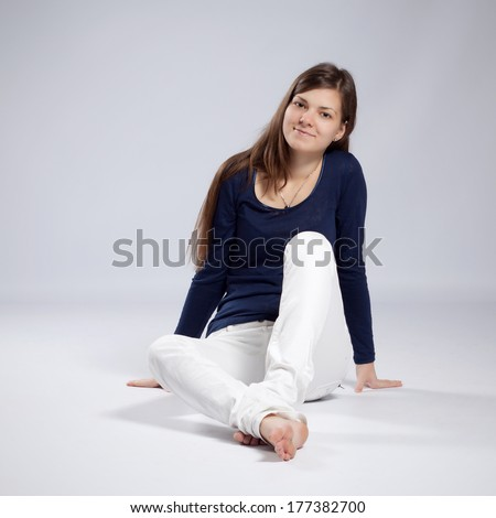 Young long-haired woman without makeup in white jeans and a blue shirt sitting on the floor