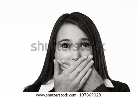 young looking woman in a suit covering her mouth with her hands - stock photo