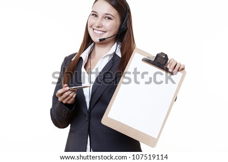 young looking woman in a suit wearing a headset holding a clip board