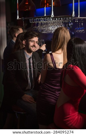 Young love birds having date in nightclub. Cute man in jeans and and black jacket dreaming about disco all night long.  - stock photo
