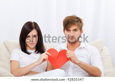 young love couple holding and break red valentine's heart together sitting on couch at home, unhappy looking at camera, valentine day love concept - stock photo