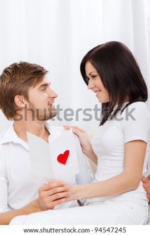 young love couple holding valentine's greeting card, note, letter with red heart, happy smile looking to each other, sitting on coach, valentine day concept