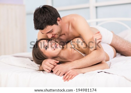 Young love couple in bed, romantic scene in bedroom - stock photo