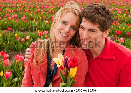 Young love couple in Dutch flower fields with colorful tulips - stock photo