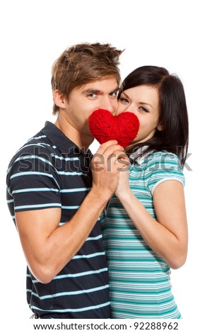 young love couple kissing behind a red heart, happy smile hug looking at camera, isolated over white background, valentine day concept - stock photo