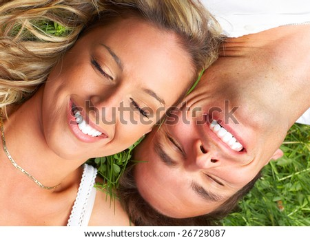 Young love couple sleeping on the green grass - stock photo