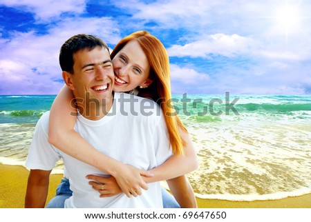 Young love couple smiling under tropical beach