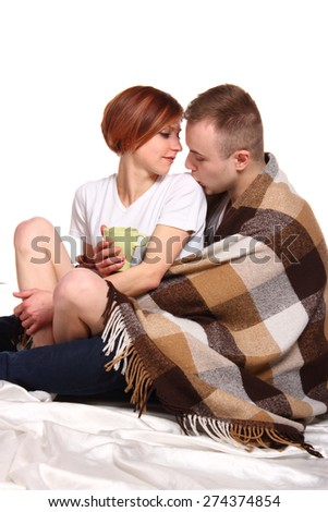 Young love couple under the covers with cup