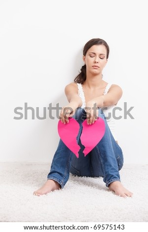 Young lovelorn female sitting on floor with paper heart in hands.? - stock photo