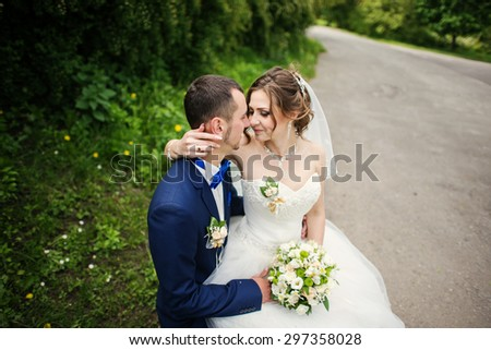 Young lovely and cheerfull wedding couple walking at the park - stock photo
