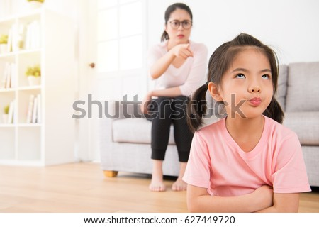 young lovely children was bored with her angry mother loudly nag feeling impatient hate annoying when mom was sitting behind her on sofa in living room at home.