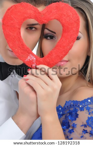 Young lovely couple holding red heart together - stock photo