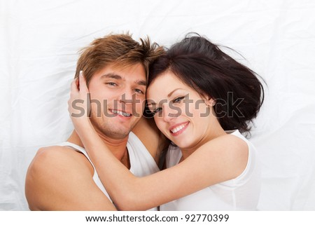 young lovely couple lying in a bed, happy smile looking at camera, top view - stock photo