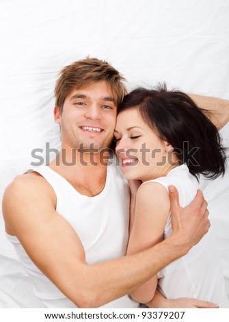 young lovely couple lying in a bed hug, happy smile looking at camera, girl closed eyes top view. - stock photo