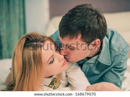 young lovely couple on a bed - stock photo