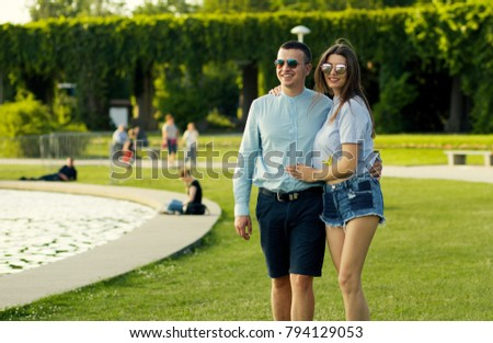 young lovely couple walk in city park
