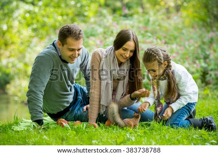 Young lovely family lying on the green grass in the park and enjoying warm weather. Feeding squirrel with the nuts, smiling and laughing. Happy healthy family on picnic. - stock photo