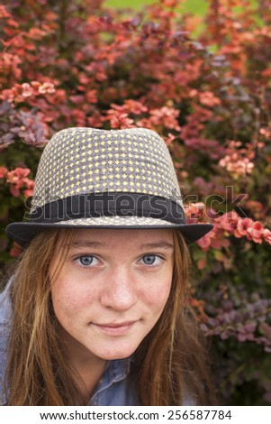 Young lovely girl in a hat, close-up portrait of a spring garden. - stock photo