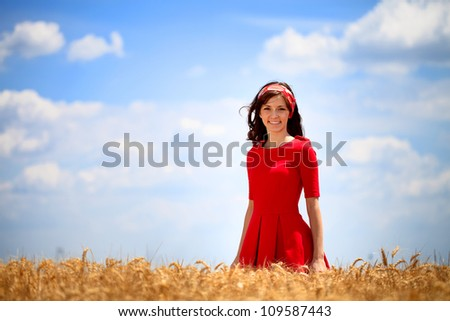 Young lovely girl in red dress standing in golden field