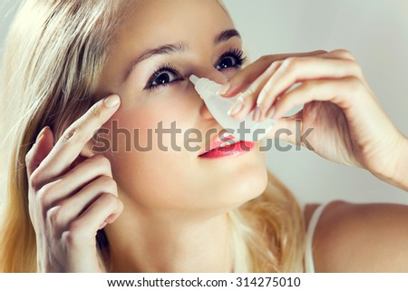 Young lovely woman dripping eyes at home - stock photo