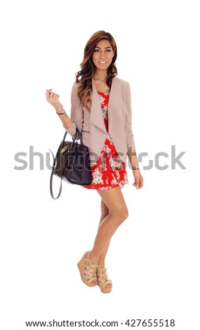Young lovely woman in a red dress and jacket holding her handbag, 