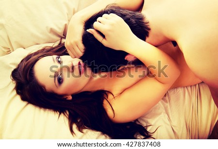 Young lovers kissing on the bed.  - stock photo