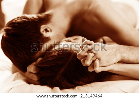 young lovers kissing on the bed focused on hand - stock photo