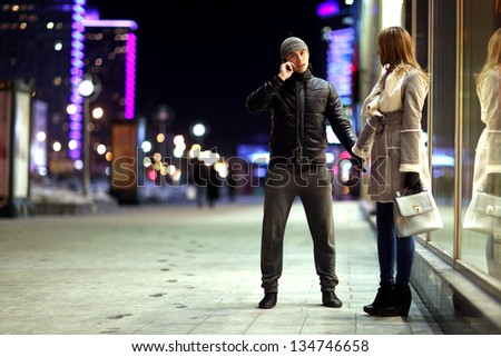 young lovers kissing on the street at night in the city, the street lights, romance - stock photo