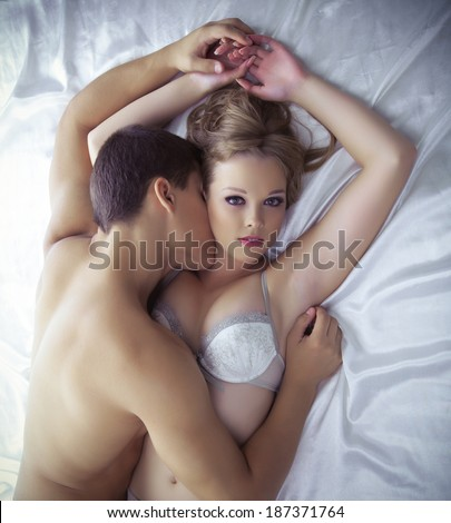 Young lovers lay in bed - only lingerie - stock photo
