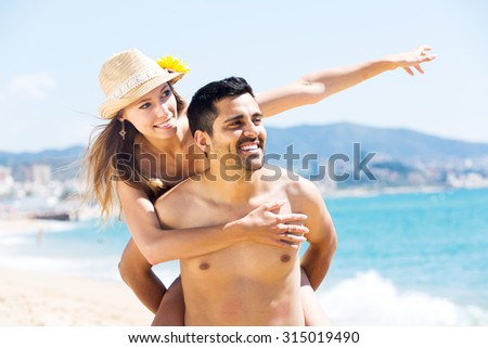 Young lovers spending time together at sea shore - stock photo