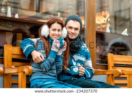 Young loving couple dressed in blue sweater sitting with knitted coffee cups on the bench near cafe in winter - stock photo
