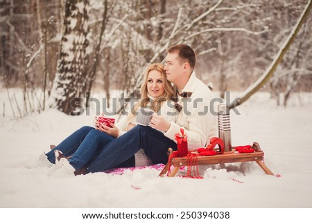 Young loving couple dressed in white sweater sitting with knitted coffee cups in the park