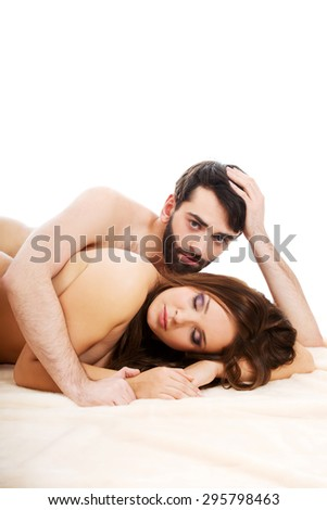 Young loving couple embracing in bed.