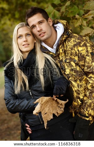 Young loving couple enjoying autumn forest, looking away.