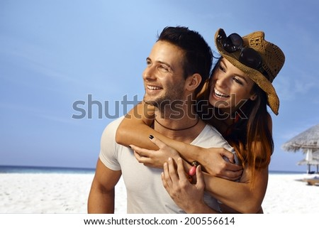 Young loving couple enjoying summer holiday on the beach, embracing, looking away.
