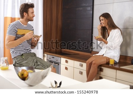 Young loving couple having breakfast in the kitchen, smiling happy. - stock photo