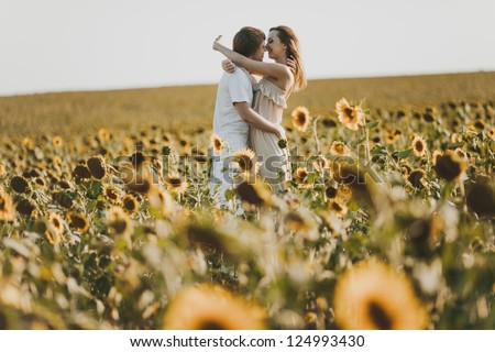 Young loving couple in field - stock photo