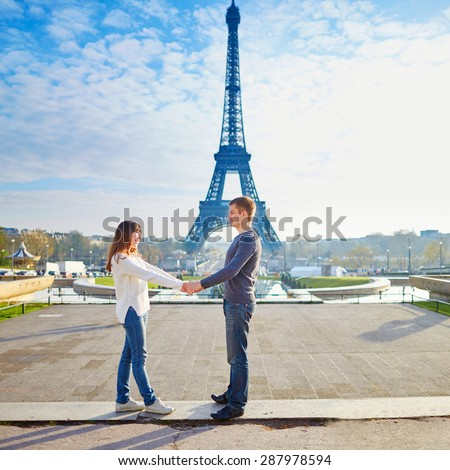 Young loving couple in Paris, holding hands near the Eiffel tower