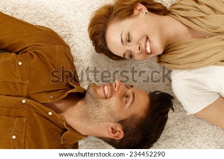 Young loving couple lying on carpet, smiling happy head by head.  . - stock photo