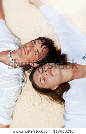 Young loving couple on sand, enjoying each other - stock photo