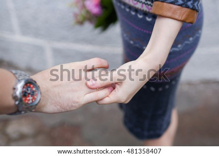 Young loving couple outdoor, holding hands . Natural light, selective focus, focus on hands