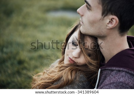 Young loving couple relaxing on grass and hugging, she is smiling and leaning on his shoulder, relationships and feelings concept - stock photo