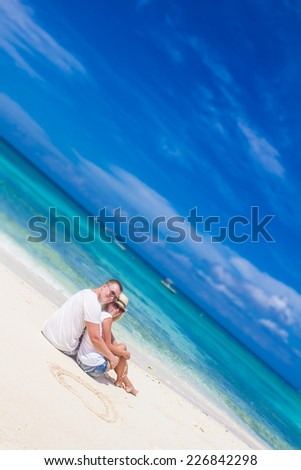 young loving couple relaxing on sand tropical beach on blue sky and sea background - stock photo