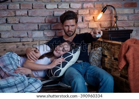 Young loving couple relaxing, watching tv at home. - stock photo