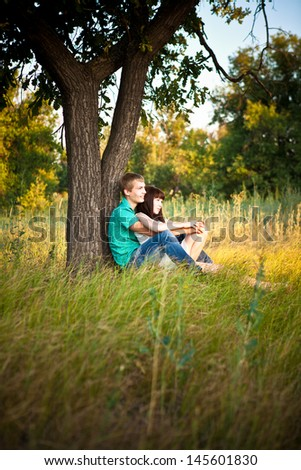 Young loving couple sitting under a tree