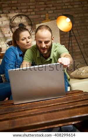 Young loving couple using laptop computer at home. - stock photo
