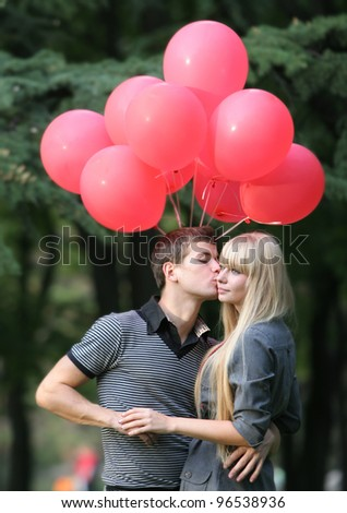 young loving couple with red balloons in park